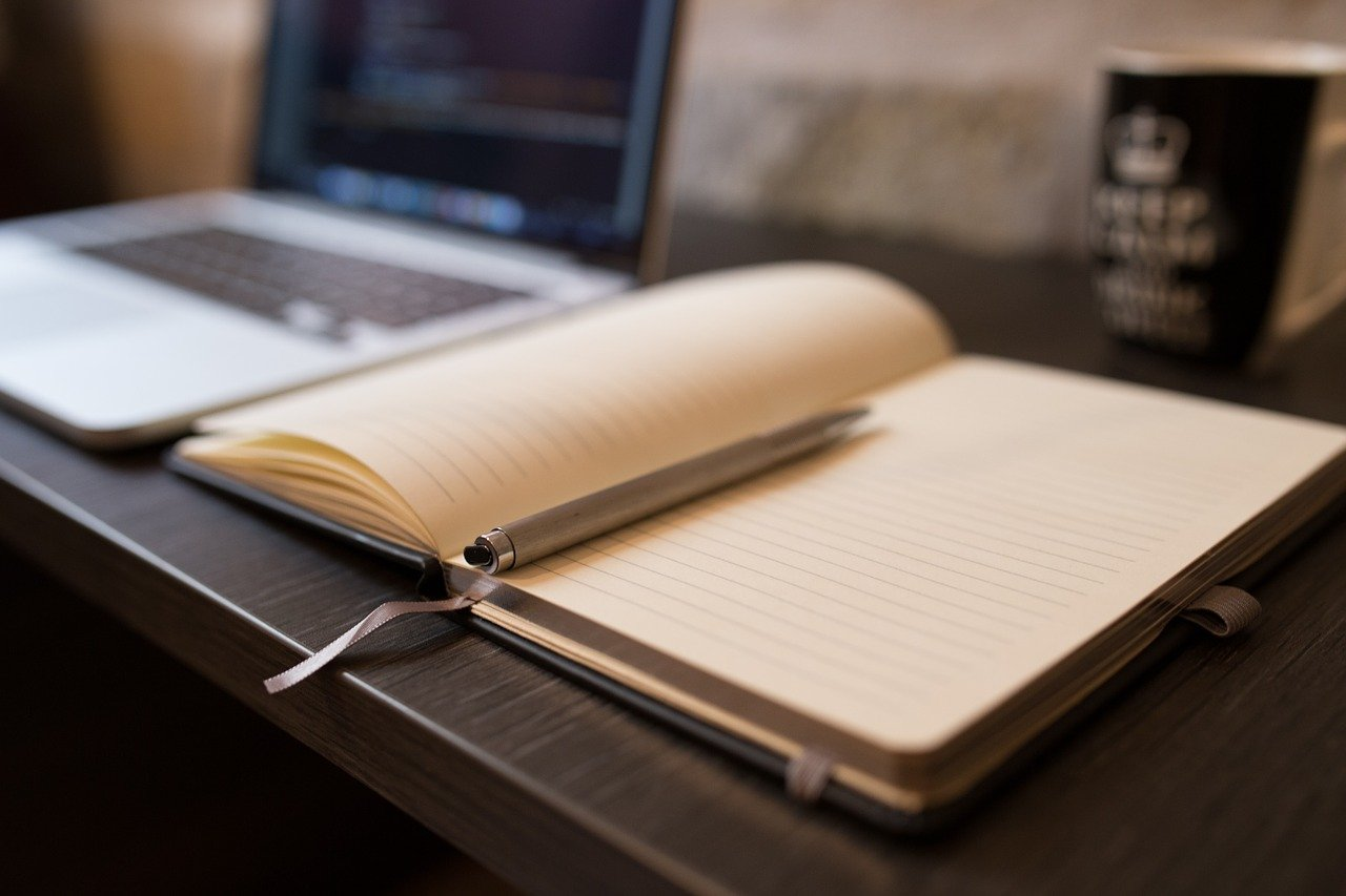 Book lying open on desk next to laptop